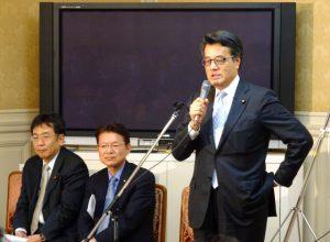 代議士会で近況報告をする岡田代表。網膜剥離を再発したほうの目は、まだぼやけているそうです。